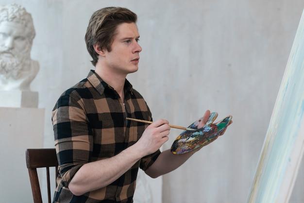 Artist man painting on canvas