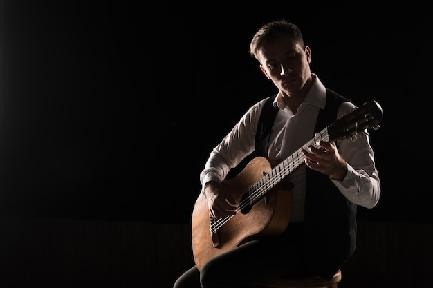 Artist man on stage playing the classical guitar copy space