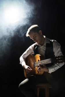 Artist man on stage playing the classical guitar
