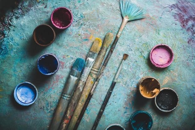 밝은 수채화 배경 위에 아티스트 페인트 브러시 및 페인트 캔