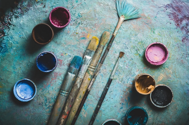 Artist paint brushes and paint cans of paint over bright watercolor background