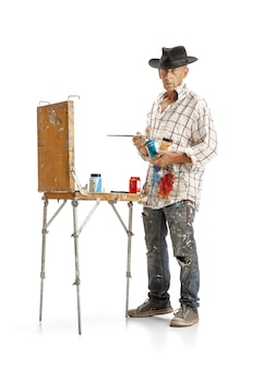 白いスタジオの背景に分離された仕事でアーティストの画家