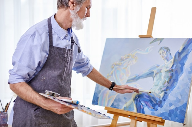 Artist painter man painting picture on canvas. happy retirement lifestyle concept