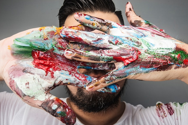 An artist painter's hand is covered with paint