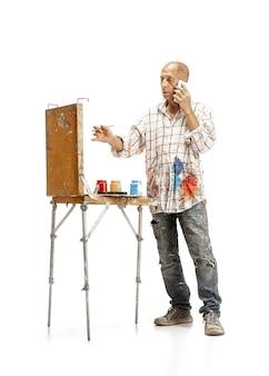 Artista pittore al lavoro isolato su bianco