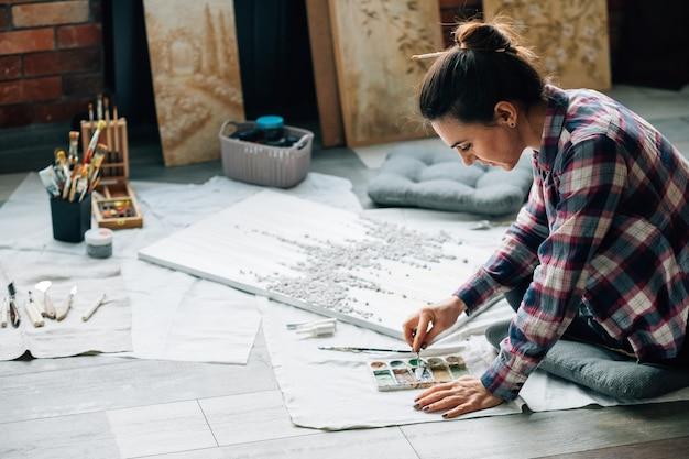 アーティストの絵画。床に帆布。スタジオスペース。個人の職場。周りのアートワークや画材。
