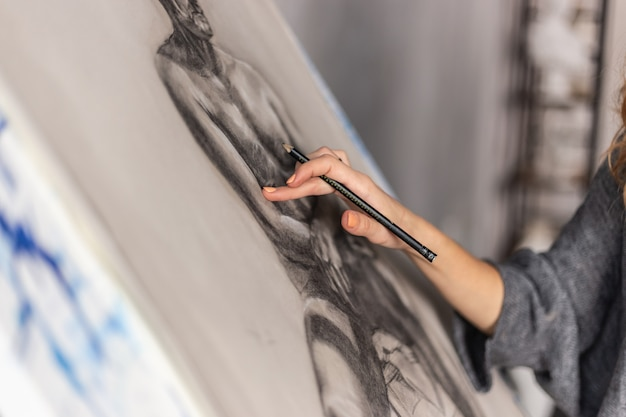 Artist painting on easel in studio. female painter seen from side.