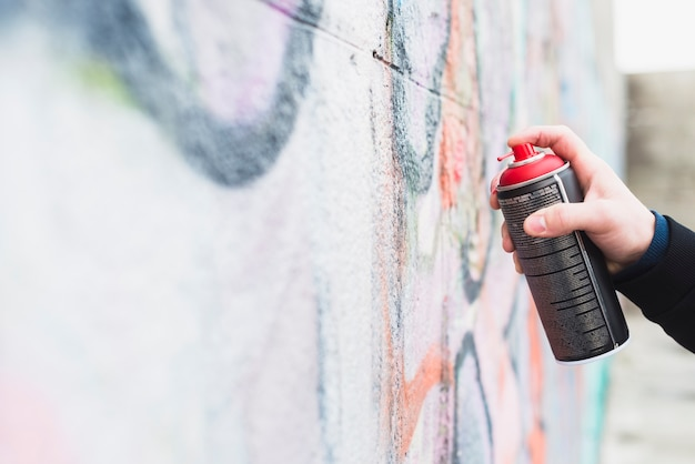 Artist painting graffiti with spray can