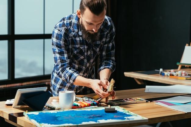 彼のスタジオワークスペースでのアーティストの絵画