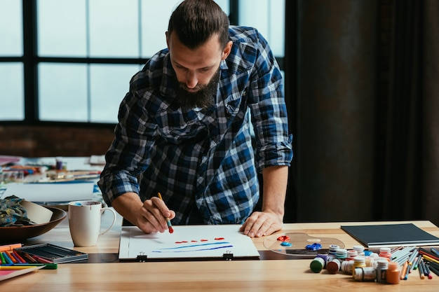 彼のスタジオワークスペースでのアーティストの絵画 Premium写真