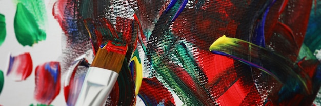 Artist painting picture with multicolored oil paints closeup