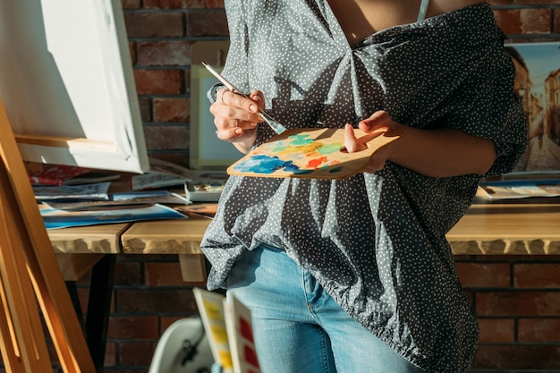 アーティストの絵画。スタジオワークスペース。木製パレットに絵の具を混ぜるイーゼルを持つ女性。