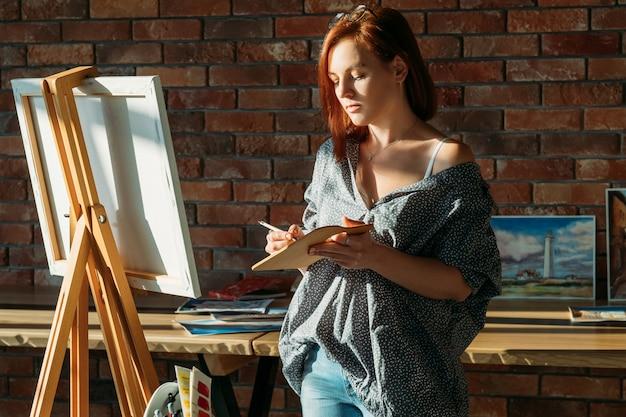 アーティストの絵画。スタジオワークスペース。木製パレットにイーゼル混色の赤毛の女性。