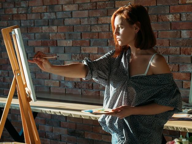 アーティストの絵画。スタジオワークスペース。キャンバスに木製パレットを描いた思いやりのある赤毛の女性。