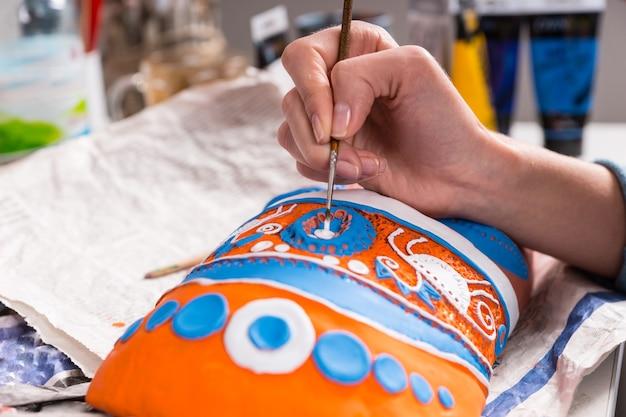 예술가는 창의성과 수공예 작업의 개념으로 수제 마스크에 화려한 장식 머리 장식을 칠하고 손과 붓을 가까이서 볼 수 있습니다.