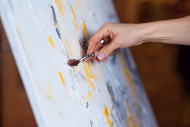 The artist paints an abstract painting using mastichin.