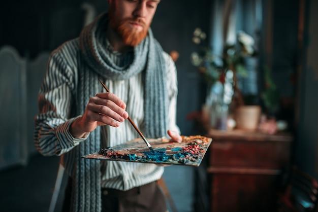 アーティストがパレット、アートスタジオに色を塗る