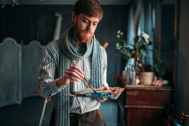 アーティストがパレットに色を塗る