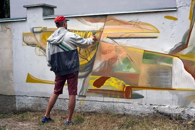 Художник рисует граффити на бетонной стене.