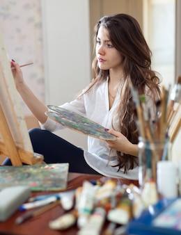 Artist paints picture on canvas with oil paints