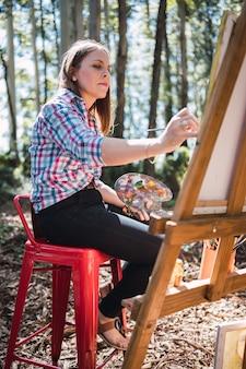 Художница рисует картину на открытом воздухе, держа в руке масляную кисть и палитру красок, воплощая свои творческие способности в жизнь.