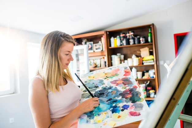 Artist paints a picture of oil paint brush in hand with palette.