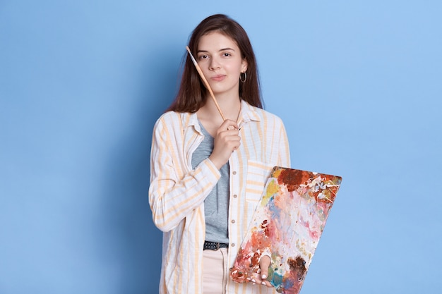 Artist paints picture, posing with pensive expression, brunette lady wearing white shirt with brush in hands.