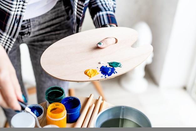 アーティストパレット。アーティストの手がパレットに絵の具を混ぜます。油絵またはアクリル絵の具。セレクティブフォーカス