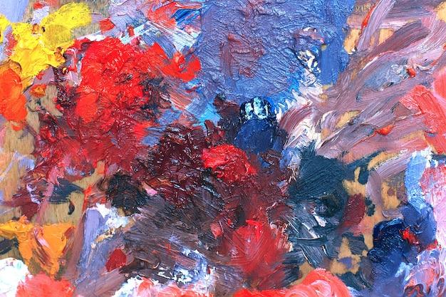 混合油絵の具とアーティストパレットキャンバス上のカラフルなブラシストロークで抽象的な背景