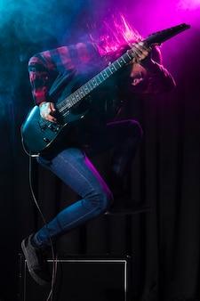 ギターを弾き、横にジャンプするアーティスト