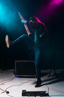 ギターを弾き、ジャンプするアーティスト