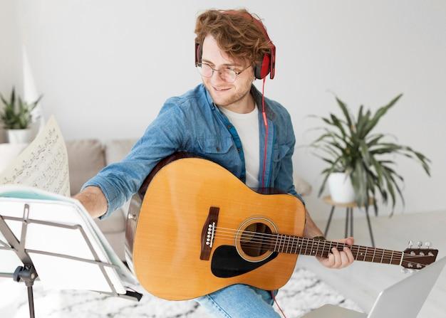 アーティストがギターを弾き、ヘッドフォンをつけている