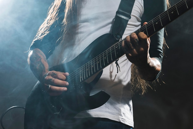 ギターのミディアムショットを演奏するアーティスト
