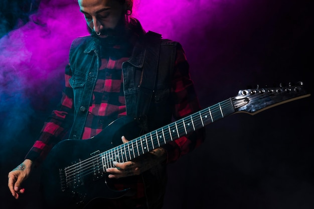 Artist playing guitar and violet stage light and smoke
