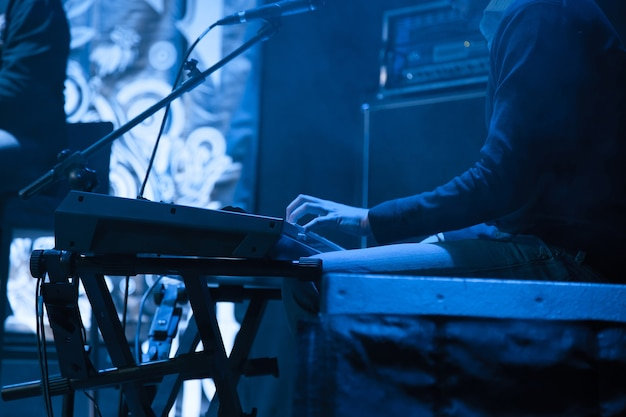 アーティストはコンサートのためにシンセサイザーで演奏します。