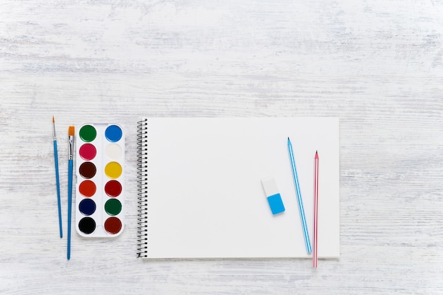 Artist's blank sketchbook on white wooden  with pencils, paints and brushes.