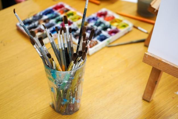Artist's brushes on his desktop. watercolor paints