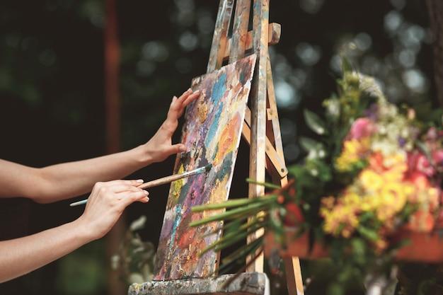 Рука художника крупным планом на стене картины