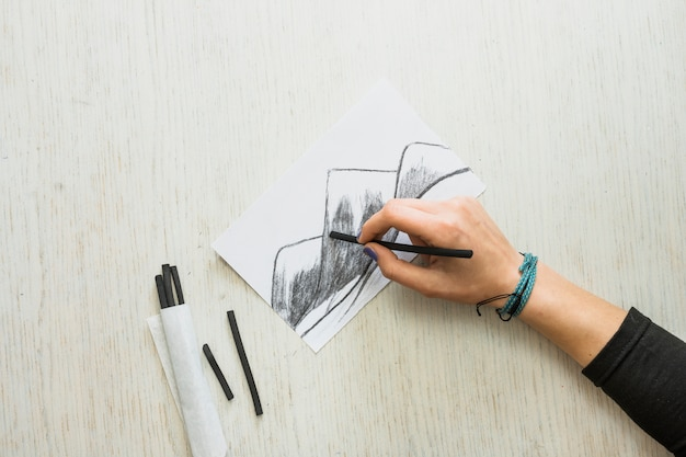 Artist's hand sketching drawing on white paper with charcoal stick