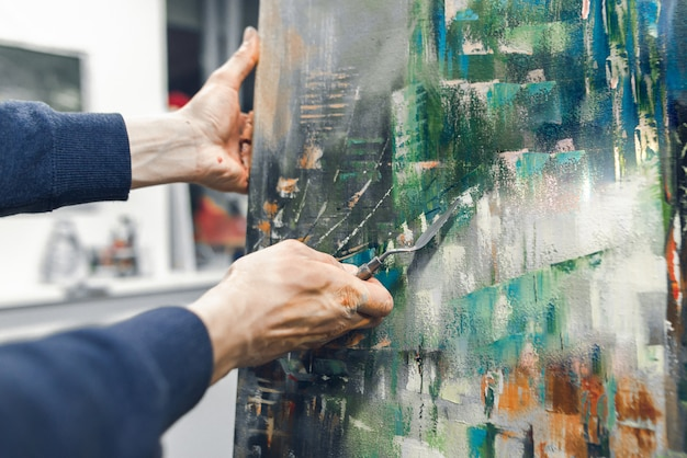 Artist's hand with a knife palette paints on the canvas