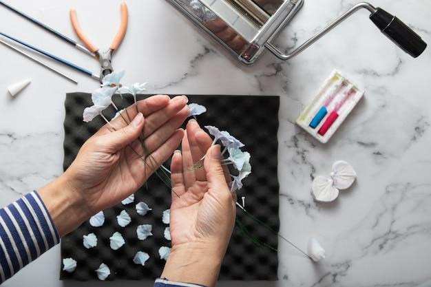 Руки художника в процессе создания цветов гортензии из полимерной глины