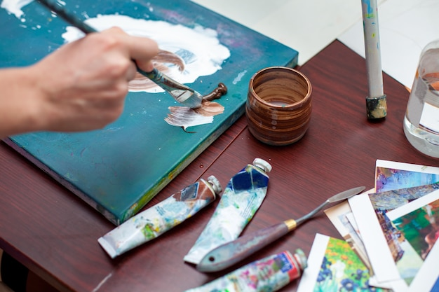 キャンバスに絵を描くアーティストの手