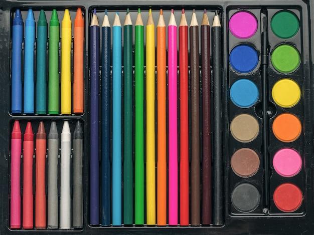 Набор художника красок, мелков и карандашей крупным планом.