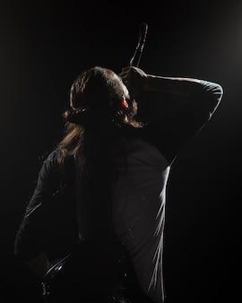Артист поет на сцене со спины