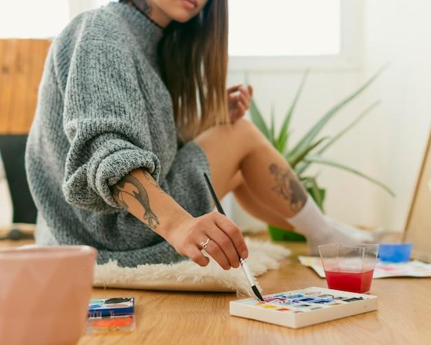 Artista seduto sul pavimento circondato da tavolozze di colori