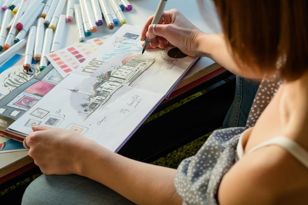 Artist sketching. workplace inspiration. woman painter drawing in sketchbook
