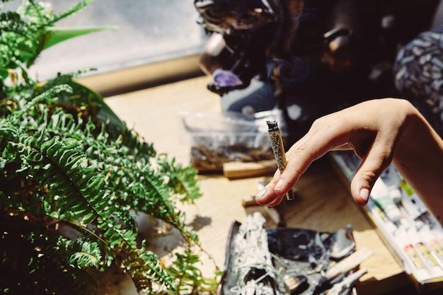 Художник курит марихуану вейп-ручкой и суставом