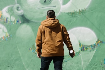 Artist standing in front of graffiti wall with aerosol can in hand
