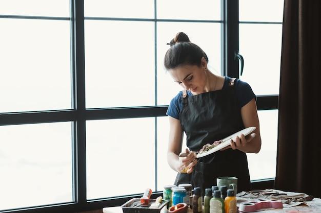 アーティストスタジオ。進行中の粘土の手工芸品。セラミックアートワーク。職場でモデリングツールを持つ黒いエプロンの女性。