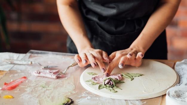 アーティストスタジオ。進行中の粘土の手工芸品。職場でモデリングツールを持つ黒いエプロンの女性。ミッドセクション。